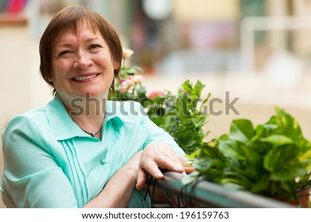 Cheerful senior woman sitting on balcony and smiling - stock photo