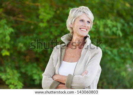 Cheerful senior woman standing with arms crossed outdoors - stock photo