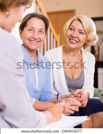 cheerful senior women consulting at insurance agent at home. Focus on the left woman - stock photo