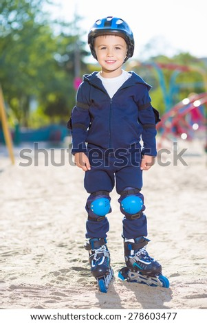 Cheerful skater boy in helmet posing on the playground - stock photo