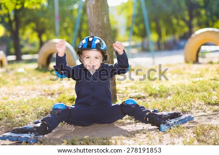 Cheerful skater boy in helmet sitting under the tree - stock photo