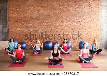 Cheerful slim girls are doing yoga - stock photo