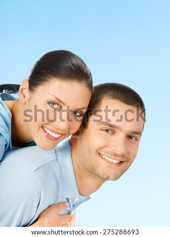 Cheerful smiling amorous couple, over blue sky background, with blank copyspace area for text or slogan - stock photo