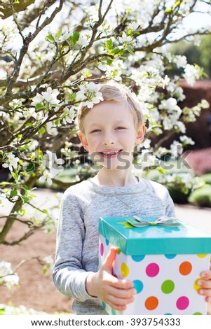 cheerful smiling boy holding colorful present for mother's day or other celebration by the blooming tree at park at spring time - stock photo