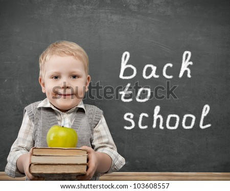 Cheerful smiling child with a book and apples stands at the blackboard. Looking at camera. School concept - stock photo