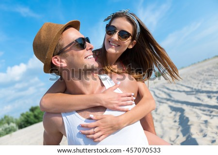 Cheerful smiling couple resting on the beach - stock photo