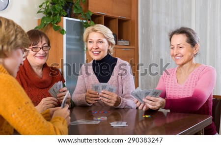 Cheerful smiling elderly female friends playing cards at home - stock photo