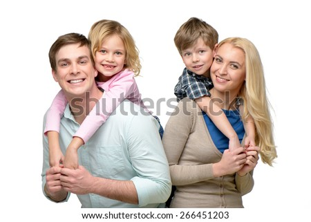 Cheerful smiling family of four having fun. Children riding piggyback on parents. Isolated on white background. Concept for happy family - stock photo
