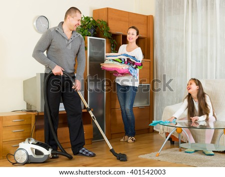 Cheerful smiling family of three tidying up a room all together. Focus on man - stock photo