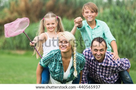 Cheerful smiling family with kids enjoying vacation in village. Focus on woman
