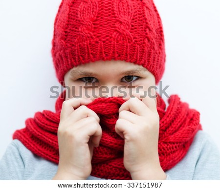 Cheerful smiling girl wearing a hat and scarf - stock photo