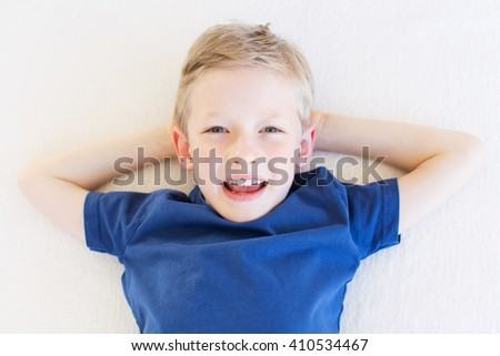 cheerful smiling little boy in blue shirt lying at the couch, positive emotion concept - stock photo