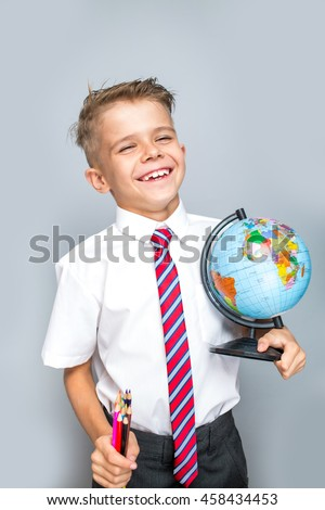 Cheerful smiling little boy on a grey background. Back to school concept - stock photo