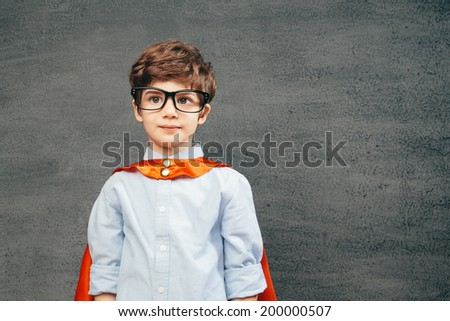 Cheerful smiling little kid (boy) against  chalkboard.  School and superhero concept - stock photo