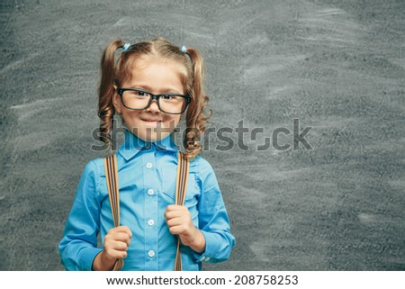 Cheerful smiling little kid (girl) against chalkboard. Looking at camera. School concept - stock photo