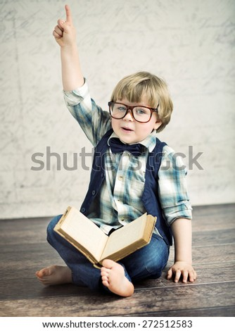 Cheerful smiling little kid with a book - stock photo