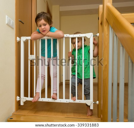 Cheerful smiling little sisters near stair gate at home