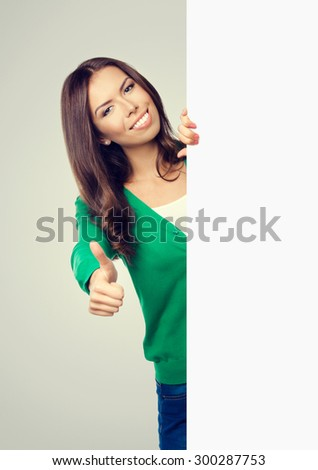 Cheerful smiling lovely woman in green casual clothing, showing blank signboard or copyspace for slogan or text, with thumb up gesture - stock photo