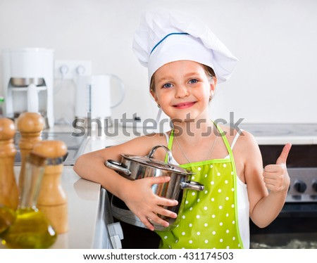Cheerful smiling preschooler posing with pan indoors - stock photo