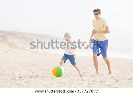cheerful smiling son and his young father playing beach ball at the beach in california - stock photo