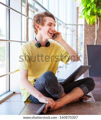 Cheerful smiling teenage boy talking by phone sitting on the floor - stock photo