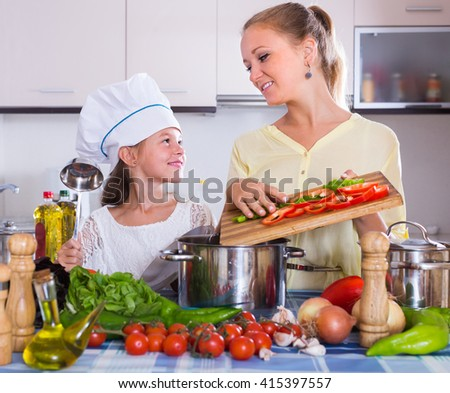 Cheerful smiling woman and her daughter with veggies at kitchen table - stock photo