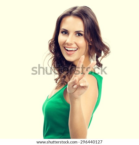 Cheerful smiling young brunette woman showing two fingers or victory gesture, in smart green casual clothing - stock photo