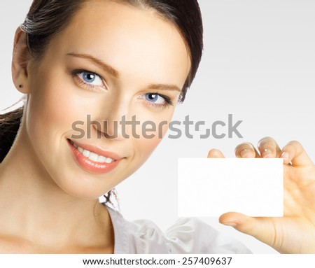 Cheerful smiling young businesswoman showing blank business or plastic credit card with copyspace area for slogan or text, on grey - stock photo