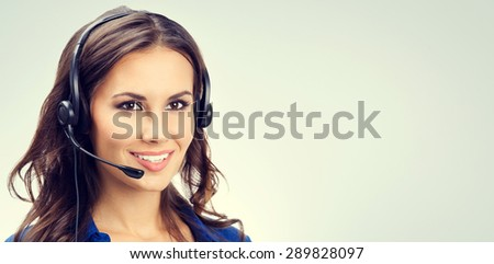 Cheerful smiling young support phone operator or businesswomen in headset, with blank copyspace area for slogan or text. Customer service concept. - stock photo