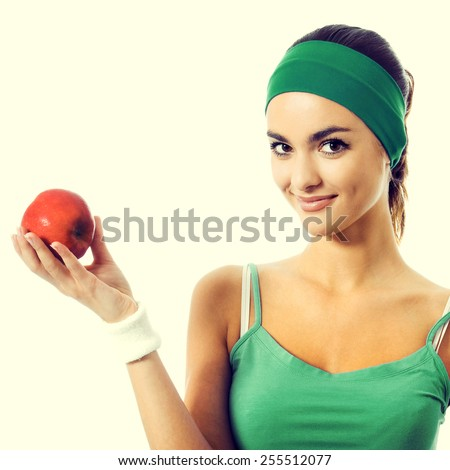 Cheerful smiling young woman in green fitness wear with apple - stock photo