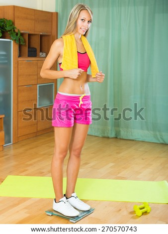Cheerful smiling young woman with weigher after morning exercises  - stock photo