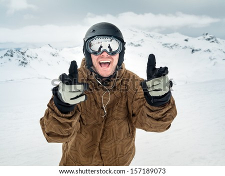 Cheerful snowboarder in protective helmet and mask showing sign happy on the background beautiful mountains - stock photo
