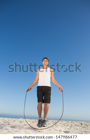 Cheerful sporty man jumping rope on the beach - stock photo
