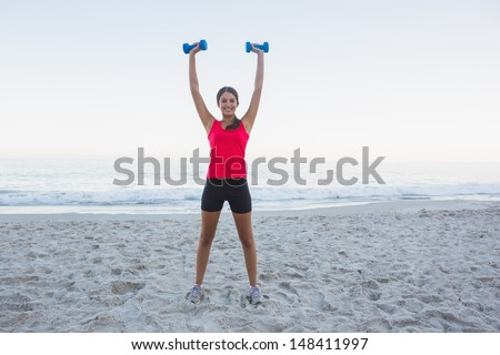 Cheerful sporty woman holding dumbbells on the beach - stock photo