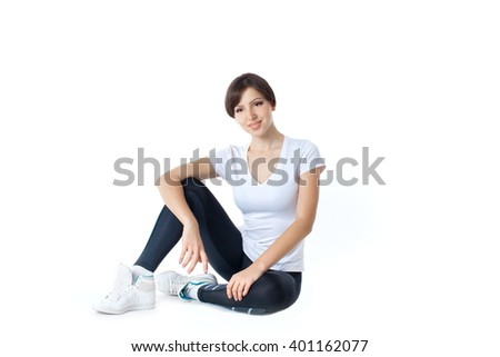 Cheerful sporty woman sitting on the floor isolated on a white background. Looking at camera - stock photo