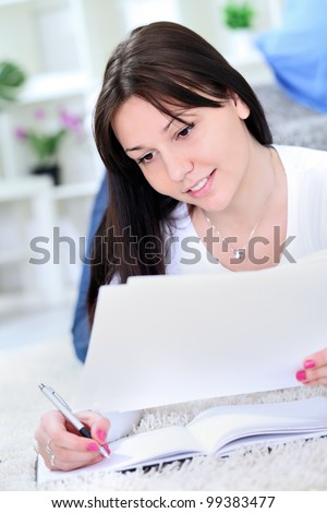 Cheerful student learning on floor - stock photo