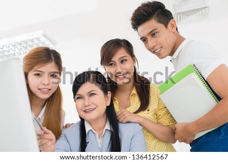 Cheerful students collaborating with their teacher to develop the project - stock photo
