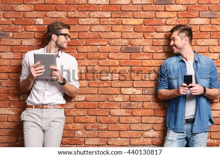 Cheerful students entertaining with contemporary technology - stock photo