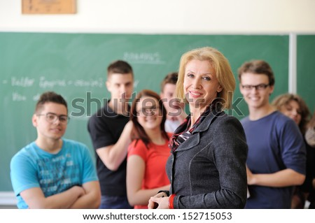 Cheerful students standing in front of a blackboard with their teacher - stock photo
