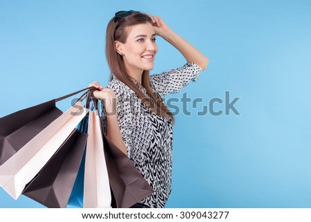 Cheerful styled woman is holding packets of bought clothing with joy. She is standing and adjusting sunglasses on her hair. The lady is smiling. Isolated and copy space in right side - stock photo