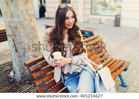 Cheerful  stylish  young woman in the street drinking morning coffee in sunshine light. Wearing cute  pink sweater, jeans. Toned colors - stock photo