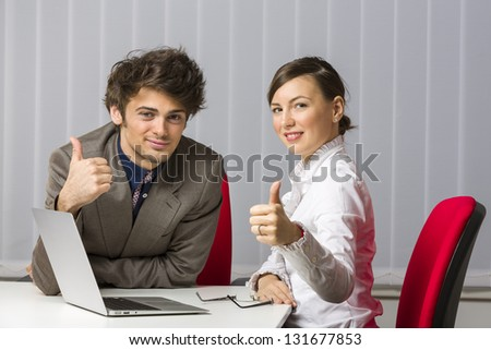 Cheerful successful business team giving the thumbs up at desk in the office. - stock photo