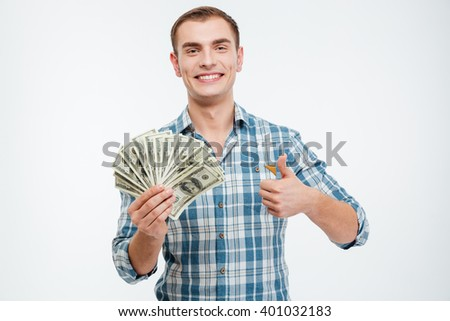 Cheerful successful young man holding money and showing thumbs up over white background  - stock photo