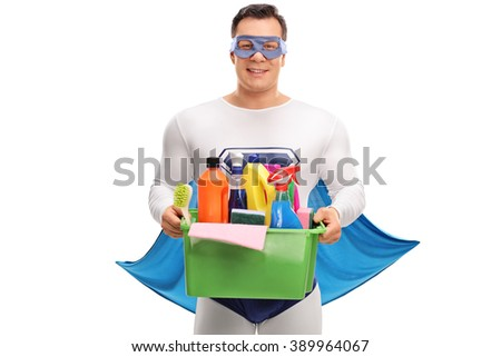Cheerful superhero holding a basket full of cleaning products and equipment isolated on white background - stock photo
