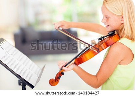 cheerful talented preteen girl playing violin at home - stock photo