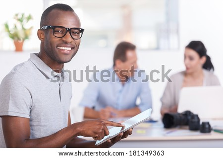 Cheerful team leader. Handsome young African man working on digital tablet and smiling while two people working on background - stock photo