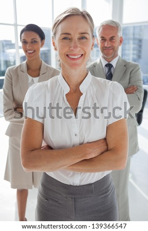 Cheerful team of business people standing together with their arms crossed - stock photo