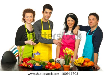 Cheerful team of four chefs standing in a line near table with vegetables and one of man pointing to table - stock photo