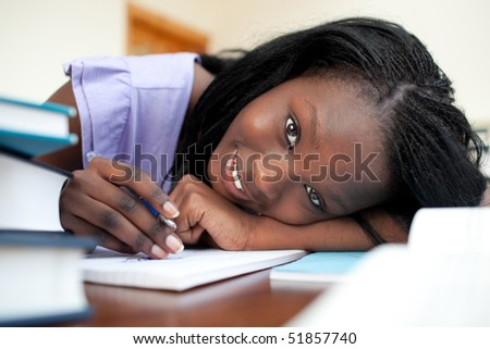 Cheerful teen girl doing her homework at home - stock photo