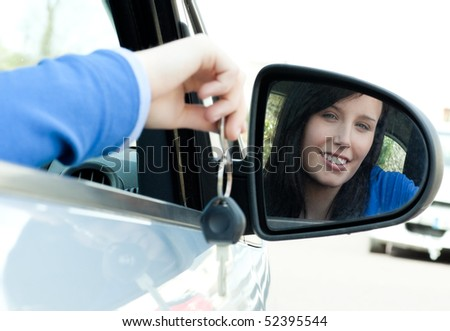 Cheerful teen girl sitting in her car holding keys after bying a new car - stock photo